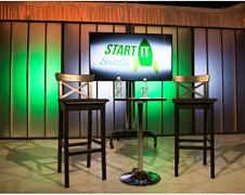 Two tall chairs sit next to a cafe table in front of the Start IT Seattle logo which is on a TV screen